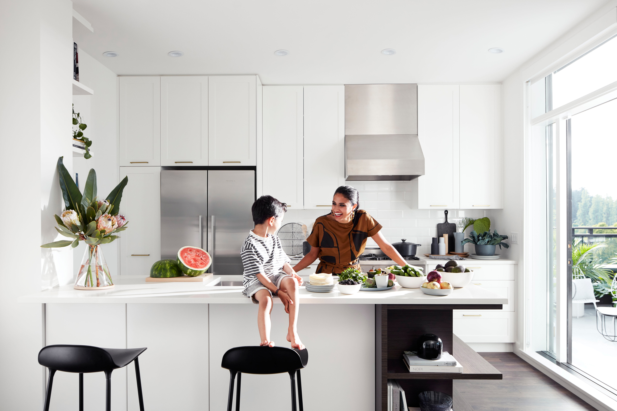 girl and young boy in kitchen talking